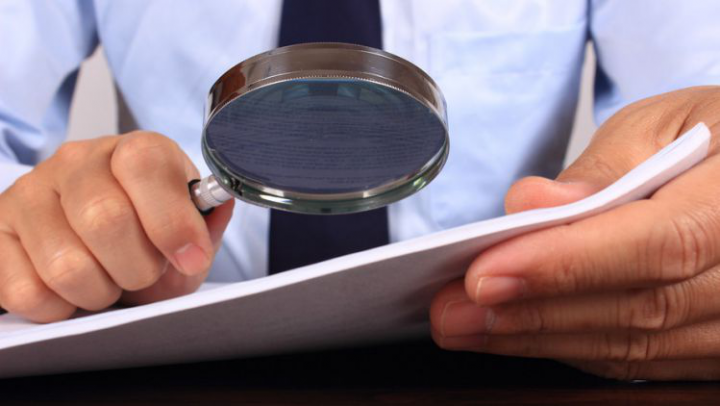 A person inspecting a background report with a magnifying glass
